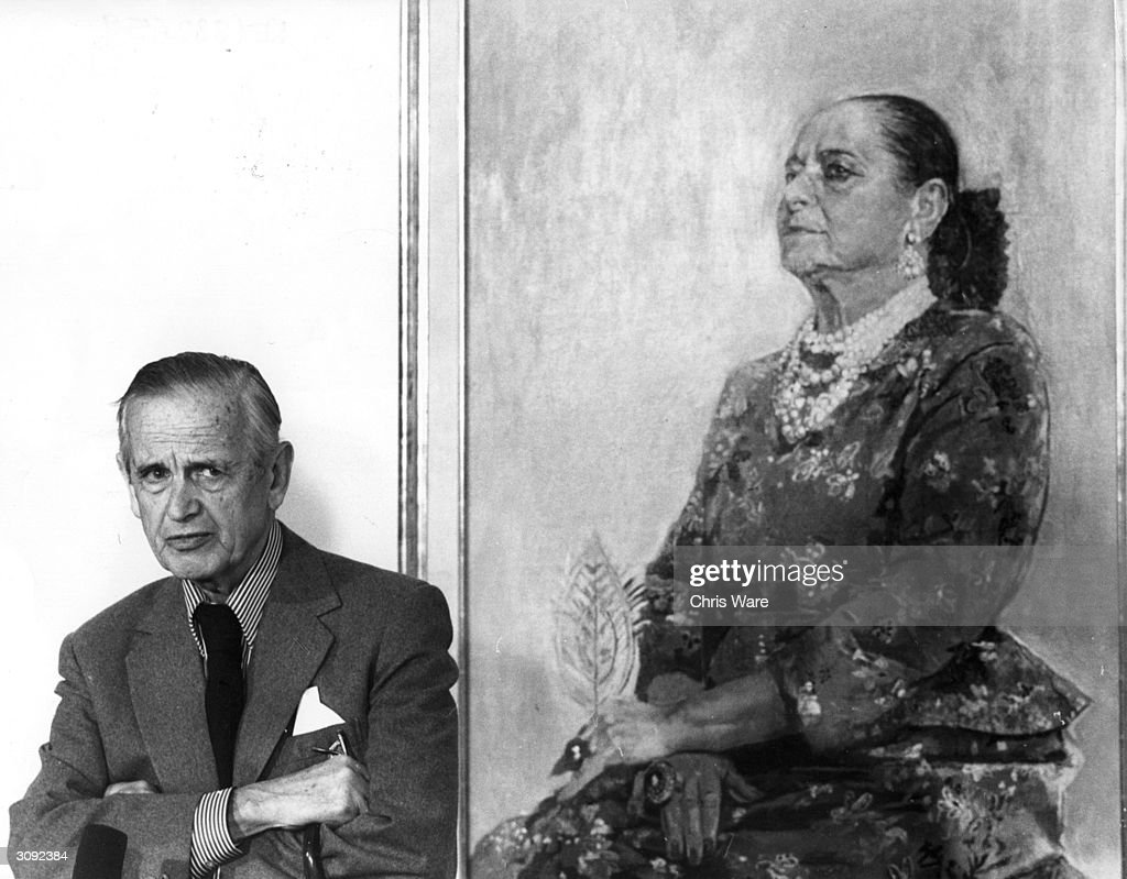Graham Sutherland (1903 - 1980), English artist and illustrator, at the National Portrait gallery in London, standing beside his painting of Helena Rubinstein.