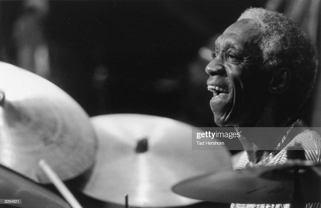 Profile headshot of American jazz musician Art Blakey (1919 - 1990) smiling while playing drums during a performance at the Stamford Center for the Arts, Stamford, Connecticut. Cymbals are visible in the foreground.