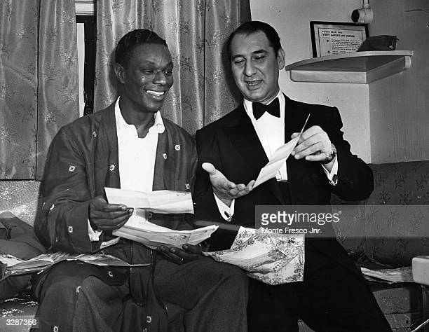 Celebrated American singer Nat King Cole reads congratulatory telegrams with comedian Henny Youngman after the success of their debut at the London...