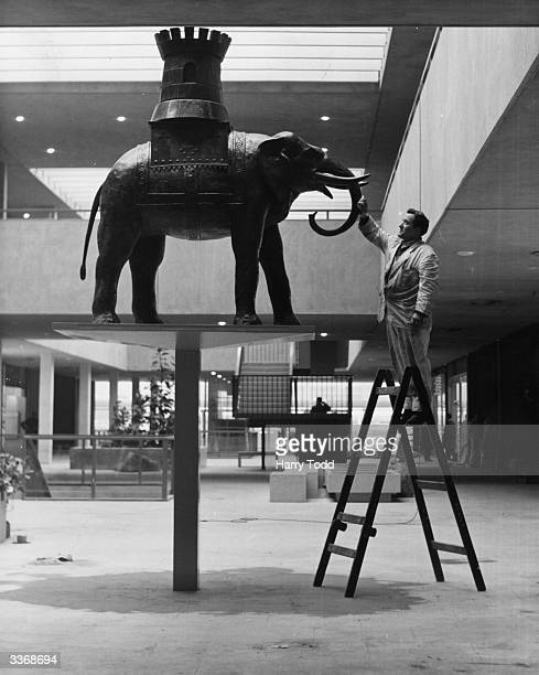 A worker cleans the original Elephant and Castle statue which formerly stood on the public house of the same name now given pride of place in the new...