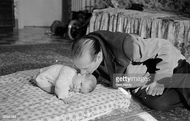 Italian film director Roberto Rossellini and husband of Ingrid Bergman kisses one of his elevenmonthold twin daughters Original Publication Picture...
