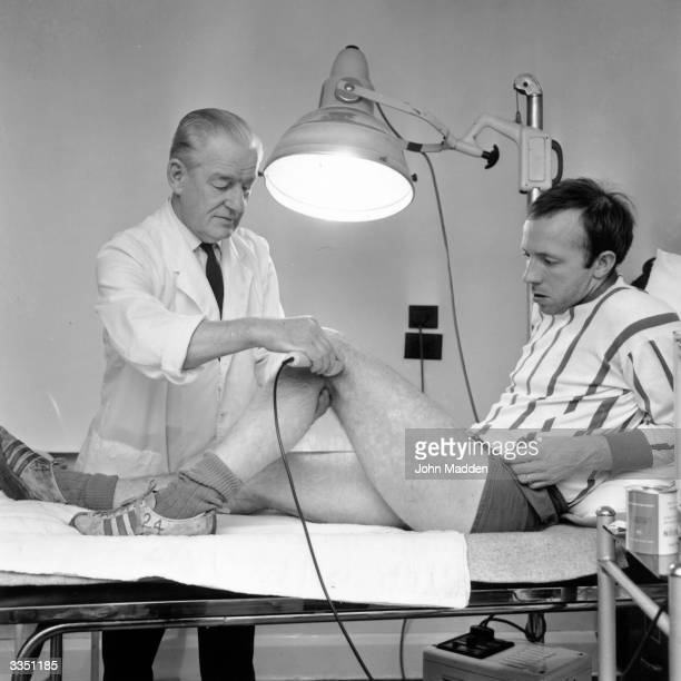 Manchester United footballer Nobby Stiles receiving treatment on his knee from the club physiotherapist Ted Dalton