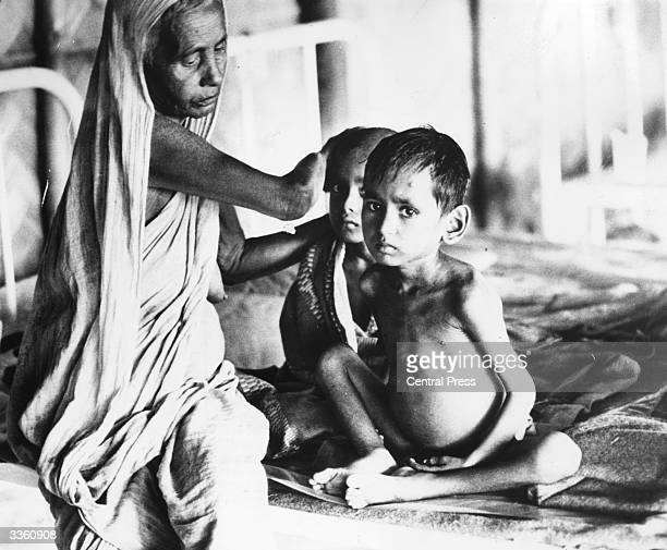 An elderly woman comforts her undernourished grandchildren in a field hospital in Calcutta having fled from East Pakistan to avoid the civil war and...