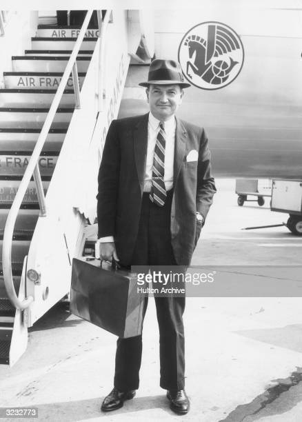 David Rockefeller president of the Chase Manhattan Bank holds a briefcase near an airplane upon his arrival from Paris at the New York International...