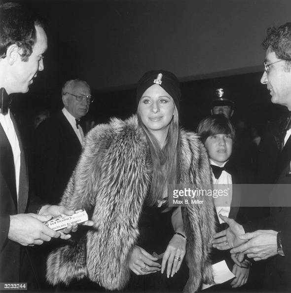 American actor and singer Barbra Streisand wearing a turban and a fur jacket surrounded by men in tuxedos at the premiere of director Sydney...