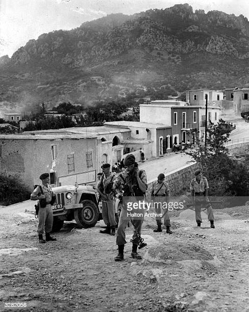 Men of the No 45 Commando use mine detectors to examine open ground for hidden arms during a surprise pounce on the Cyprus village of Akanthou The...