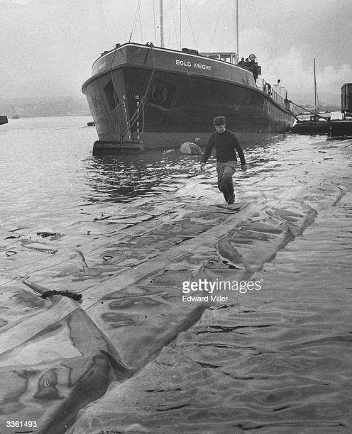 An engineer runs along the top of a 'sea serpent' floating dracone a nylon oilcarrier capable of carrying over 300 tons of oil as it is filled from a...