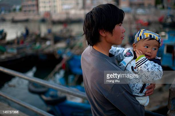 A 23yearold Chinese fisherman Li Xuesong coming from Ziyang of Sichuan province holds his baby waiting for his fishing boat at a port on May 21 2012...