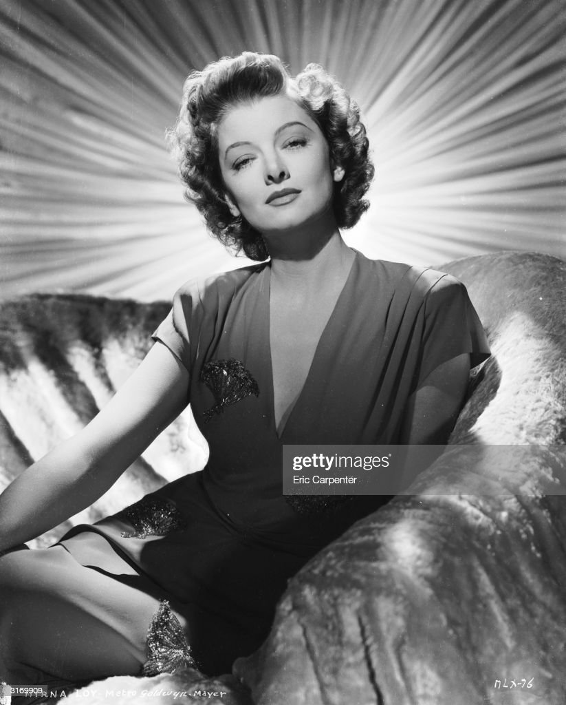 American actress <a gi-track='captionPersonalityLinkClicked' href=/galleries/search?phrase=Myrna+Loy&family=editorial&specificpeople=93857 ng-click='$event.stopPropagation()'>Myrna Loy</a> (1905 - 1993) sitting on a covered sofa with a curtain with a bright sunshine design behind her.