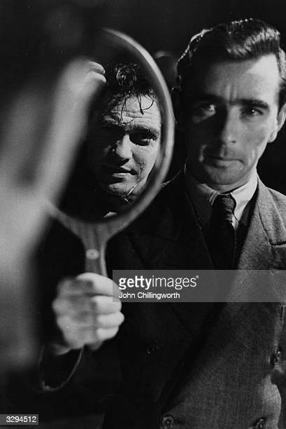 Makeup assistant Les Dawson holds up a mirror for Irish actor Richard Todd whilst preparing him for a scene in the Associated British film 'Portrait...