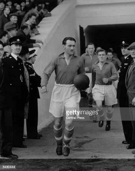 The Liverpool captain P H Taylor leads his team out