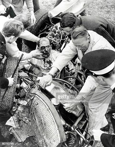 24th April 1962 British racing car driver Stirling Moss is tended in his wrecked Lotus after crashing at the Goodwood racing circuit