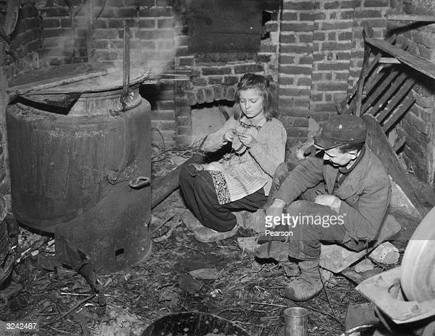 A German girl knits while her brother repairs a pair of shoes he has found in the streets of Berlin