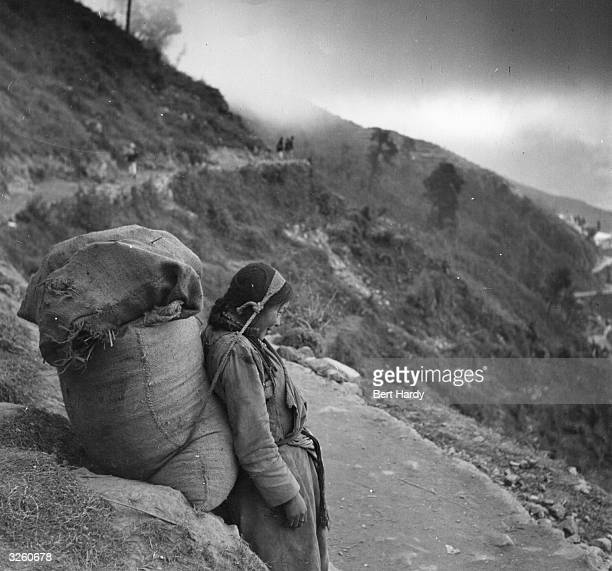 A heavilyburdened Nepalese woman rests as she journeys across the mountains on foot after a landslide closed the road to Darjeeling in India Original...