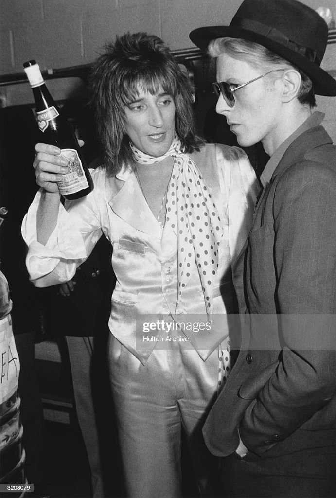 British singer <a gi-track='captionPersonalityLinkClicked' href=/galleries/search?phrase=Rod+Stewart&family=editorial&specificpeople=160467 ng-click='$event.stopPropagation()'>Rod Stewart</a> holds a bottle of Blue Nun wine and talks with British singer <a gi-track='captionPersonalityLinkClicked' href=/galleries/search?phrase=David+Bowie&family=editorial&specificpeople=171314 ng-click='$event.stopPropagation()'>David Bowie</a> backstage at Madison Square Garden, where Stewart performed, New York City. Stewart is wearing matching satin pants and vest, with a satin shirt and polka-dot scarf. Bowie is wearing a suit with a fedora hat and aviator sunglasses.