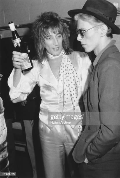 British singer Rod Stewart holds a bottle of Blue Nun wine and talks with British singer David Bowie backstage at Madison Square Garden where Stewart...