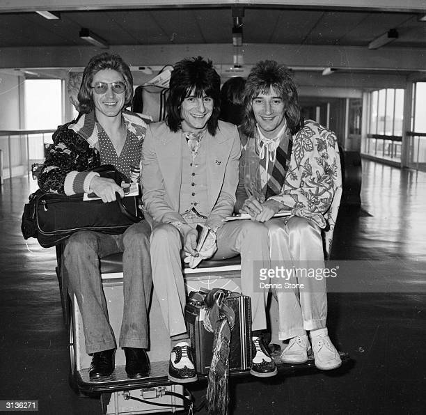 Members of The Faces on a luggage cart at London Airport Kenny Jones Ron Wood and Rod Stewart