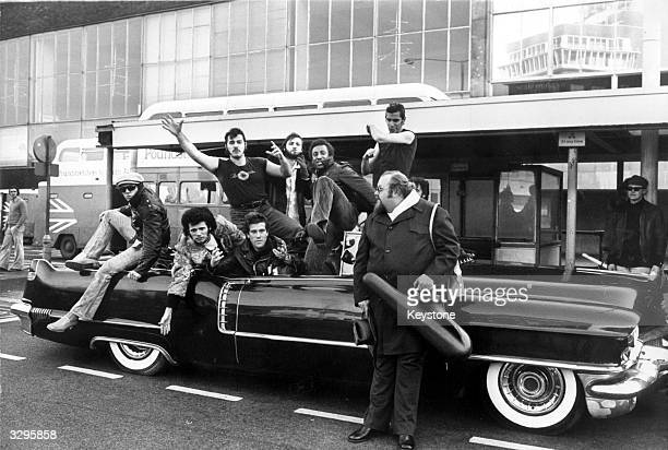 Members of the American rock 'n' roll revival group Sha Na Na in a vintage 1950's Cadillac on their arrival at Heathrow airport
