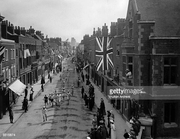 A general view of the Marathon event at the 1908 London Olympics with the competitors running along Eton High Street at Baldwin's Bridge lined with...