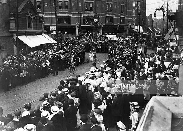 A large crowd on the streets of London watch as a competitor rounds a corner during the Marathon at the 1908 London Olympics accompanied by two...