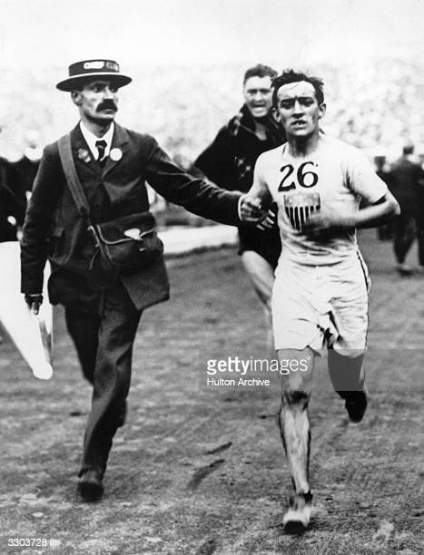 An official runs alongside John Hayes of the USA on his way to completing the Marathon at the 1908 London Olympics Hayes won the Gold Medal after...