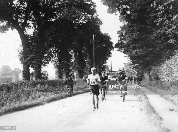Dorando Pietri of Italy on his way to the stadium during the Marathon at the 1908 London Olympics Despite finishing first he was disqualified for...