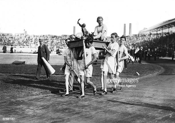 John Hayes of the United States is carried on a table by his team mates on a lap of honour around the White City Stadium after winning the Marathon...