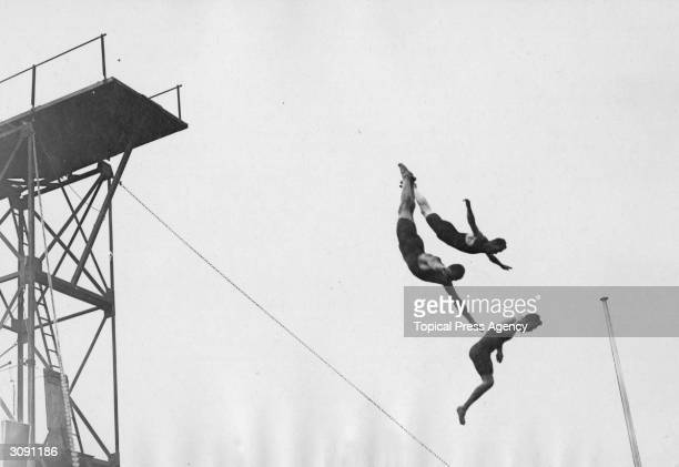 Three divers in midair action during a diving display at the 1908 London Olympics