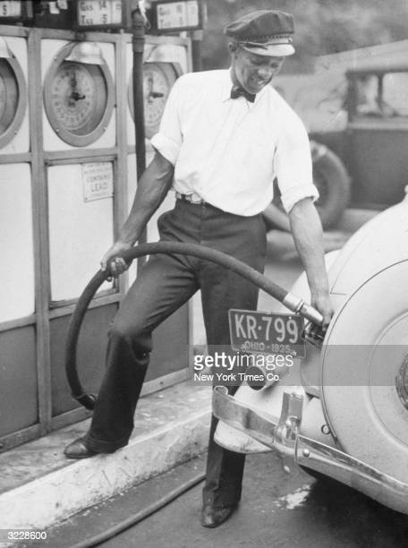 AfricanAmerican athlete Jesse Owens fills up a car at a petrol station in his a uniform of cap shirt and bow tie Owens worked as a petrol pump...