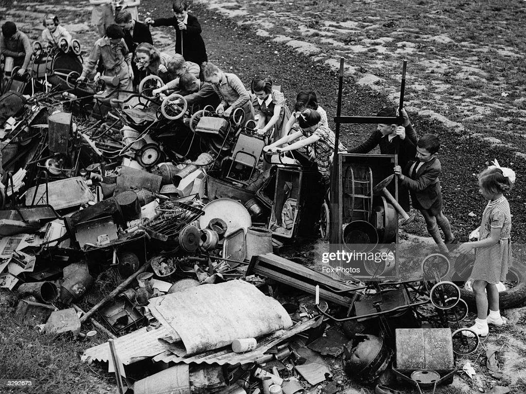 Children emptying pramloads of salvage they have collected onto a scrap heap