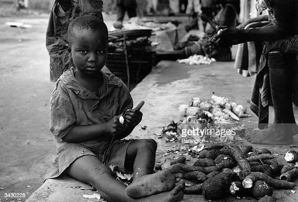 A starving Biafran child sits by a pile of yams The state tried for independence from Nigeria resulting in war and starvation of its Ibo population