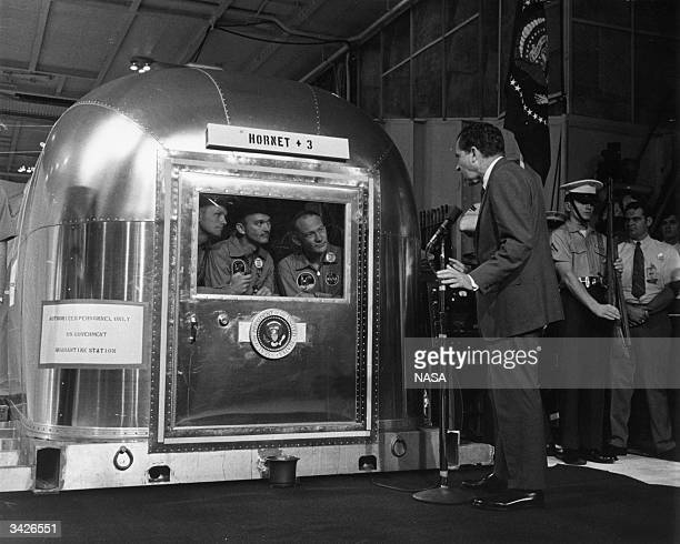 President Richard M Nixon addresses Astronauts Neil Armstrong Michael Collins and Edwin Aldrin in their Mobile Quarantine Facility aboard the USS...