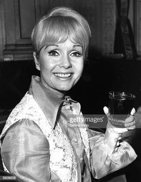 American actress and singer Debbie Reynolds drinking a coke at the London Palladium where she is appearing in her own show