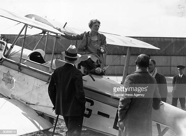 American aviatrix Amelia Earhart talking to friends from the cockpit of her Moth on the day of her trip to Northolt