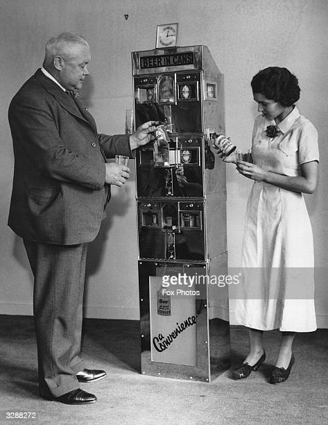 A canned beer machine being tested out in London The customer inserts 6d waits for the coin to drop and pulls out a sealed can of beer A woman is...