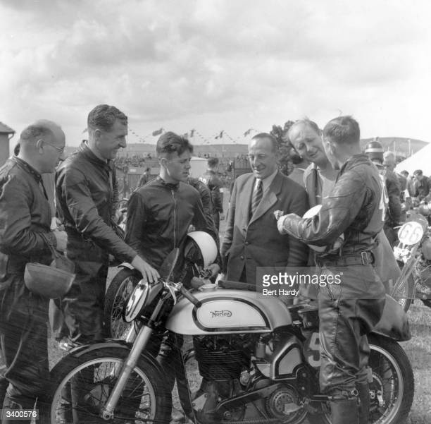 Geoffrey Duke with his Norton No 57 talking to his team mates at the Isle of Man Tourist Trophy Races Original Publication Picture Post 5069 The...