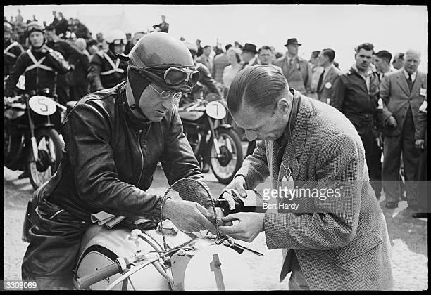 Motorcycle rider H L Daniell before the start of the Isle of Man Tourist Trophy Race fixing his 499 Norton bike Original Publication Picture Post...
