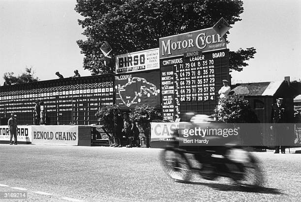 One of the 4000 motorcylists taking part in the Isle of Man Tourist Trophy races speeds past a position board Original Publication Picture Post 5069...