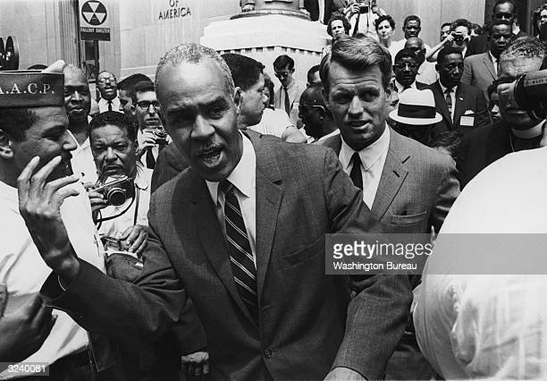 NAACP executive secretary Roy Wilkins walks in front of US attorney general Robert Kennedy during a NAACP march in front of the Justice Building in...