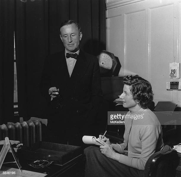 English novelist Ian Fleming best known for the character James Bond dictating to his secretary in his study
