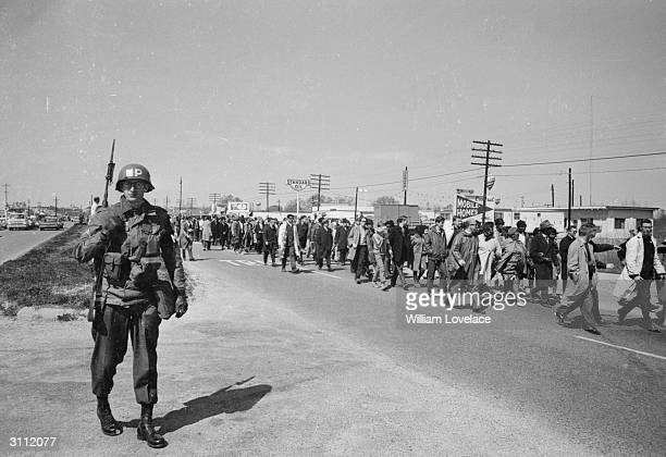 A military policeman with fixed bayonet keeps pace with the protesters in the Alabama civil rights march which was led by Dr Martin Luther King