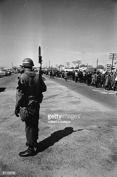 A soldier with fixed bayonet watches marchers in the Alabama civil rights march which was led by Dr Martin Luther King