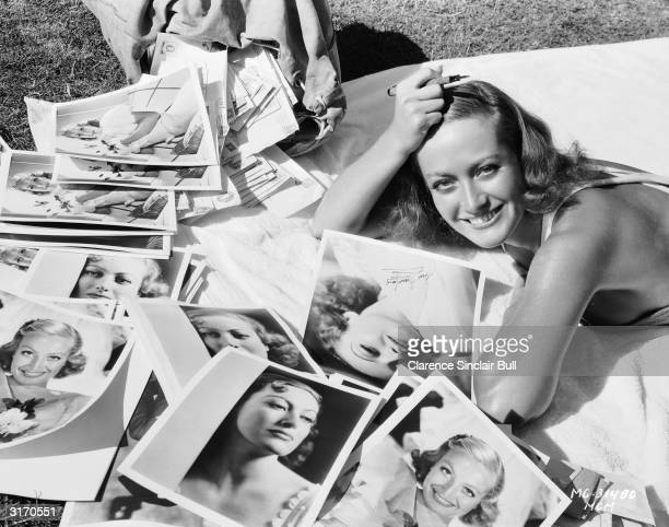 American actress Joan Crawford answers a sack of fan mail and autographs photographs to enclose with the replies