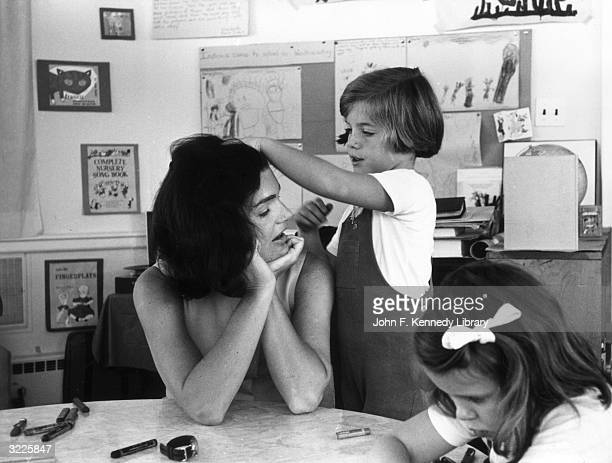 American First Lady Jacqueline Bouvier Kennedy sits at a classroom table as her daughter Caroline Kennedy runs her hand through her mother's hair...