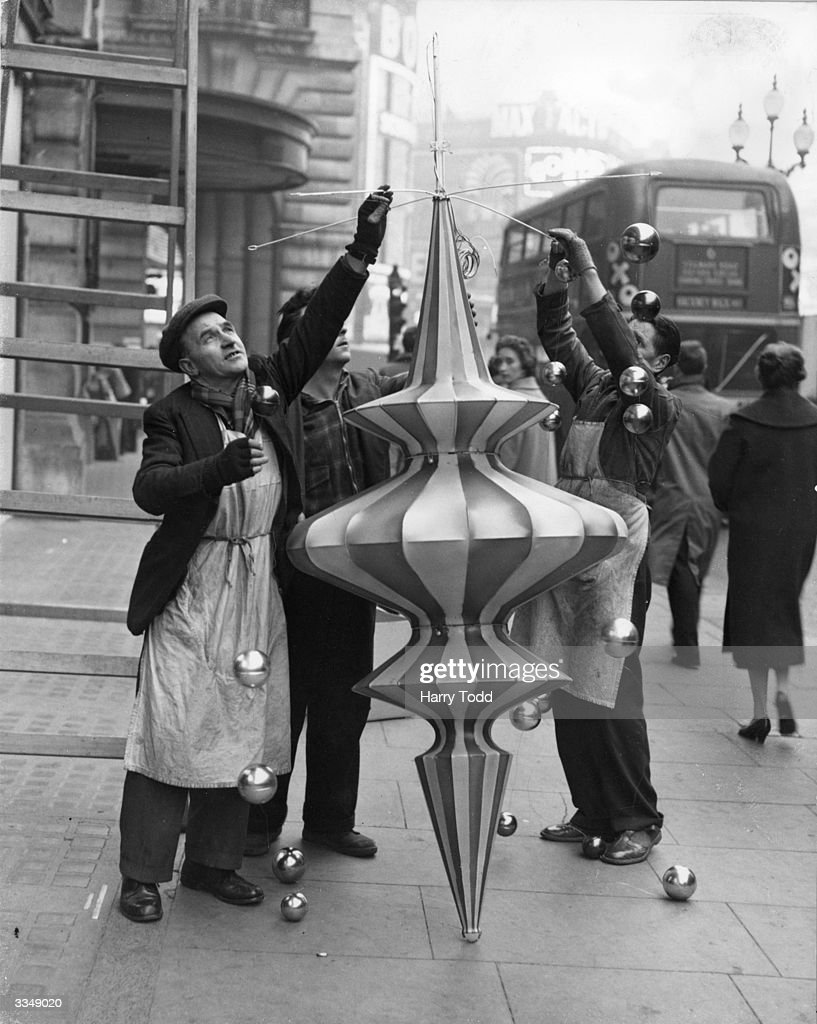 Workmen assembling a large christmas decoration before mounting it on Regent Street Central London