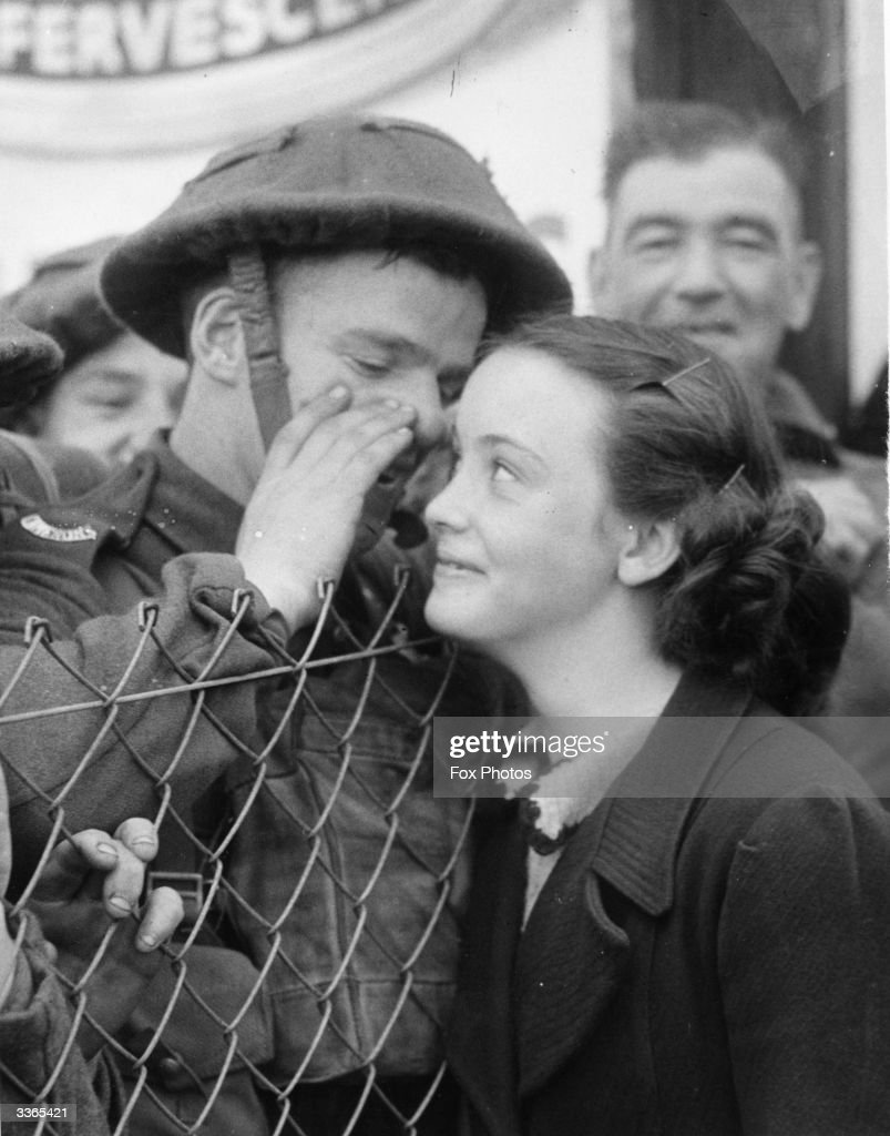A British soldier whispers into the ear of a loved one as he leaves for the Front.