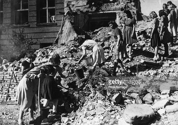 School girls from Augusta School in the US sector of Berlin work as a chain gang to clear rubble from a bombed part of their school at the end of WW...