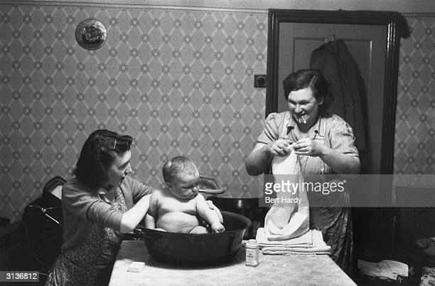 Pearl Wilson of Lambeth London helps her mother bathe her baby sister Gillian in a bowl on the table Baby powder soap and nappy are to hand Original...