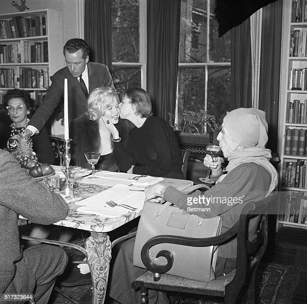 As famed Danish author Isak Dinesen sips champagne author Carson McCullers gives Marilyn Monroe a kiss of greeting at Miss McCullers' home here Feb 5...