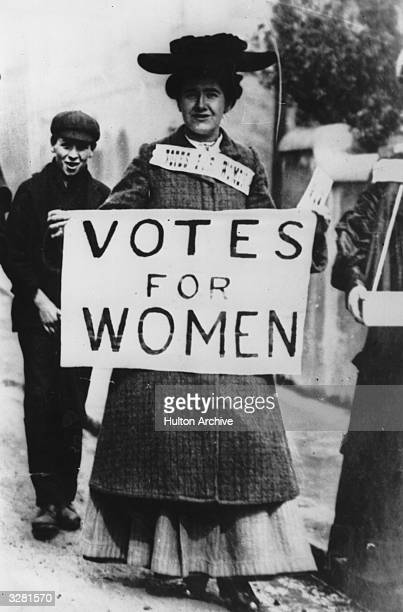 Tess Billington carries a banner enscribed with the suffragette slogan 'Votes For Women' during a demonstration in the Ladies Gallery in the House of...